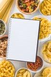 Vari tipi di pasta italiana e di libri di cucina in bianco immagine stock libera da diritti