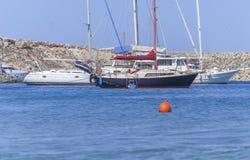 Vari vanno in automobile la barca nautica messa in bacino al mare blu il giorno di estate Fotografia Stock