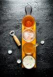 Vari vetri di birra su un tagliere di legno con l'apri fotografie stock