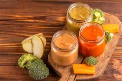 A variação pureed o comida para bebê nos frascos de vidro com ingredientes imagens de stock