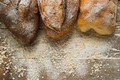 Variações do pão na parte superior da tabela de madeira com farinha Fotos de Stock