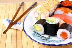 Variações do sushi com hashis e o caviar vermelho Fotografia de Stock Royalty Free
