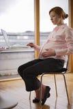 Variações grávidas e trabalhando fotografia de stock