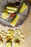 Varia miscela di pasta su fondo rustico di legno, sui cucchiai di legno, sul peperone delle spezie, sulla foglia di alloro, sulla Fotografia Stock Libera da Diritti