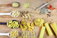 Varia miscela di pasta su fondo rustico di legno, sui cucchiai di legno, sul peperone delle spezie, sulla foglia di alloro, sulla Immagine Stock