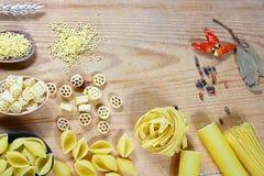 Varia miscela di pasta su fondo rustico di legno, sui cucchiai di legno, sul peperone delle spezie, sulla foglia di alloro, sulla Fotografie Stock
