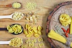Varia miscela di pasta su fondo rustico di legno, sui cucchiai di legno, sul peperone delle spezie, sulla foglia di alloro, sulla Immagine Stock Libera da Diritti