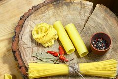 Varia miscela di pasta su fondo, sul peperone delle spezie, sulla foglia di alloro, sulla dieta e sul concetto rustici di legno d Immagini Stock Libere da Diritti