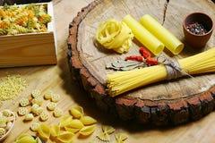 Varia miscela di pasta su fondo, sul peperone delle spezie, sulla foglia di alloro, sulla dieta e sul concetto rustici di legno d Fotografia Stock