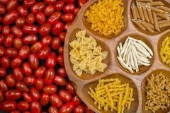 Varia miscela di pasta sulla ciotola di legno, piccolo primo piano rosso dei pomodori Fotografia Stock Libera da Diritti