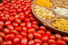 Varia miscela di pasta sulla ciotola di legno, piccolo primo piano rosso dei pomodori Fotografia Stock