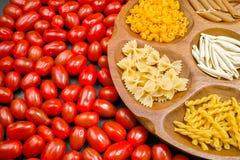 Varia miscela di pasta sulla ciotola di legno, piccolo primo piano rosso dei pomodori Immagini Stock