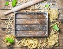 Varia pasta italiana cruda casalinga e vassoio di legno nel centro Immagine Stock