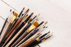 Varia raccolta dei pennelli sulla tavola di legno Immagine Stock