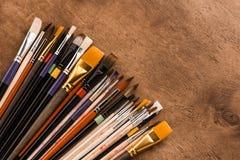 Varia raccolta dei pennelli sulla tavola di legno marrone Immagine Stock
