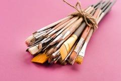 Varia raccolta legata dei pennelli sul rosa Fotografia Stock Libera da Diritti