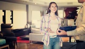 Variantes de offre de meubles de vendeur à la femme dans le salon image stock