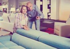 Variantes de offre de meubles de vendeur à la femme positive dans le salon Photographie stock