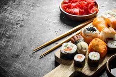 Variants of types of sushi, maki and rolls on a cutting Board with ginger and soy sauce. On dark rustic background stock photography