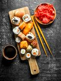 Variants of types of sushi, maki and rolls on a cutting Board with ginger and soy sauce. On dark rustic background stock image