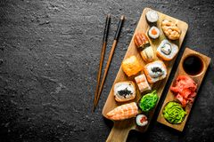 Variants of types of sushi, rolls and maki on a cutting Board with sticks. On black rustic background royalty free stock photo