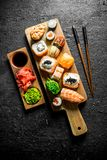 Variants of types of sushi, rolls and maki on a cutting Board with sticks. On black rustic background royalty free stock photography