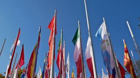 Varias astas de bandera con muchas banderas en el viento
