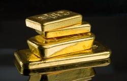 Varias barras de oro de diverso peso en una superficie oscura del espejo imagenes de archivo