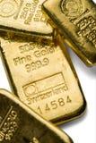 Varias barras de oro echadas de diverso peso en un fondo blanco foto de archivo