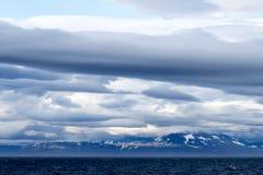 Varias capas de nubes sobre las montañas en Svalbard, Noruega imagenes de archivo