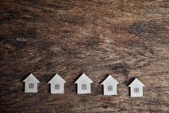 Varias casas de la cartulina en un fondo de madera Fotografía de archivo libre de regalías