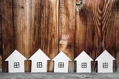 Varias casas de la cartulina en un fondo de madera Foto de archivo
