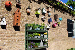 Varias casas del pájaro en una pared de ladrillo Imagenes de archivo