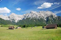 Varias chozas de madera en un prado verde delante de las montañas en las montañas bávaras Foto de archivo libre de regalías