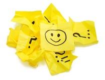 Varias etiquetas engomadas amarillas machacadas, una con sonrisa Imágenes de archivo libres de regalías