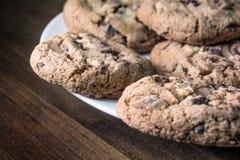 Varias galletas del chocolate que mienten al borde de una placa blanca en una tabla de madera del vintage Fotos de archivo