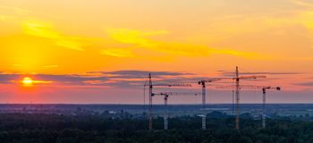 Varias grúas de construcción en el fondo del cielo colorido de la puesta del sol fotografía de archivo