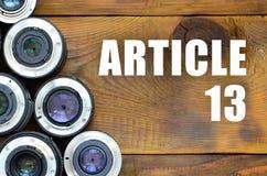 Varias lentes fotográficas e inscripción del artículo 13 en fondo de madera foto de archivo libre de regalías