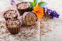 Varias magdalenas del chocolate en el tablero blanco con las flores Foto de archivo libre de regalías