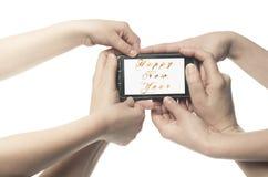 Varias manos que sostienen un teléfono con la Feliz Año Nuevo de las palabras brillantes escrita en el fondo blanco Imagenes de archivo