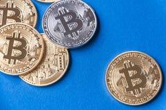 Varias monedas de bitcoins en un fondo azul con un oro y monedas de los bitcoins que caen de sus bolsillos El concepto de cripta Imágenes de archivo libres de regalías