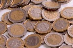Varias monedas euro en diversas posiciones respecto a un fondo blanco fotos de archivo