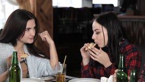 Varias muchachas comen la pizza y beben la cerveza de las botellas en el restaurante Risa de la charla y celebrar almacen de metraje de vídeo