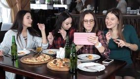 Varias muchachas comen la pizza y beben la cerveza de las botellas en el restaurante Risa de la charla y celebrar almacen de video