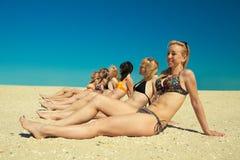 Varias muchachas en el bikiní que se sienta en la playa arenosa Fotografía de archivo libre de regalías