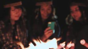Varias muchachas felices se están sentando al lado de una hoguera en la noche y utilizan smartphones Miran la foto, sonrisa almacen de video