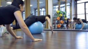 Varias mujeres jovenes se colocan en rodillas del fitball durante el entrenamiento almacen de video