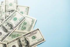 Varias notas de cientos dólares americanos sobre fondo azul claro Concepto fotos de archivo