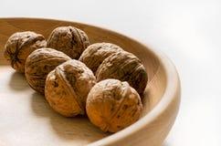 Varias nueces enteras en cuenco de madera en el fondo blanco Foto de archivo libre de regalías