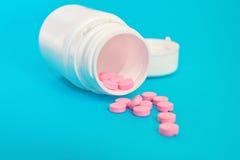 Varias píldoras rosadas vertidas fuera de una botella blanca en Backgrou azul Imagenes de archivo